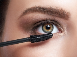 Close-up of young woman applying mascara on eyelashes by cosmeti